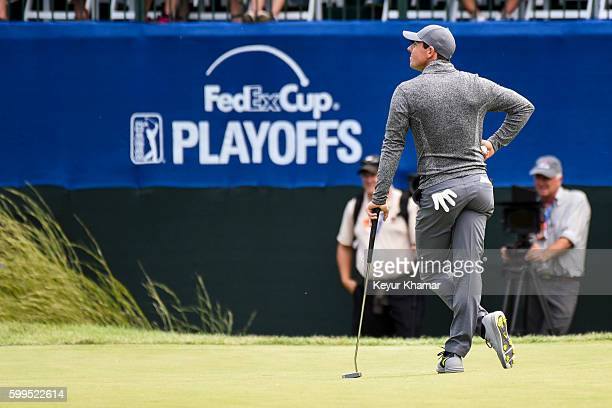 Rory McIlroy of Northern Ireland stands near the FedExCup Playoffs logo on the 16th hole green during the final round of the Deutsche Bank...