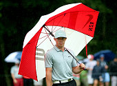 Rory McIlroy of Northern Ireland stands under an umbrella on the 15th green during the second round of the 96th PGA Championship at Valhalla Golf...