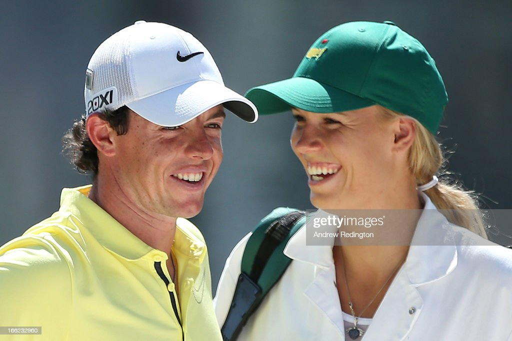 Rory McIlroy of Northern Ireland stands with his caddie Caroline Wozniacki during the Par 3 Contest prior to the start of the 2013 Masters Tournament...