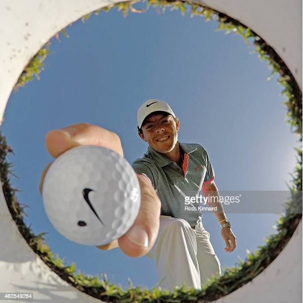 Rory McIlroy of Northern Ireland takes a ball out of the hole on the practice putting gree during the third round of the Omega Dubai Desert Classic...