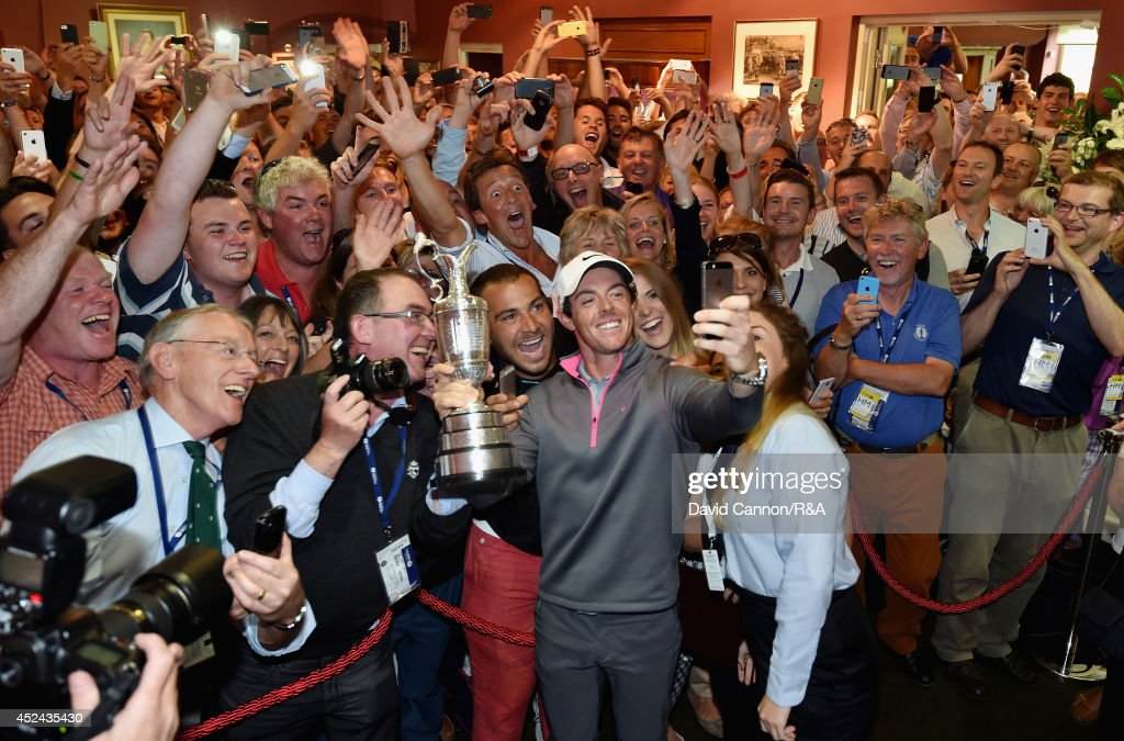 Rory McIlroy of Northern Ireland takes a selfie with the Claret Jug and members of Royal Liverpool in the clubhouse after his two-stroke victory in The 143rd Open Championship at Royal Liverpool on July 20, 2014 in Hoylake, England.