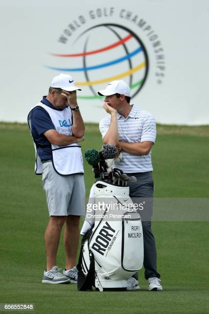 Rory McIlroy of Northern Ireland talks with his caddie on the 12th hole of his match during round one of the World Golf ChampionshipsDell...