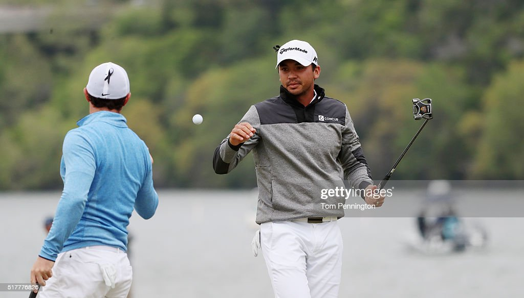 Rory McIlroy of Northern Ireland tosses a golf ball to Jason Day of Australia on the 14th hole during their semifinal match at the World Golf...