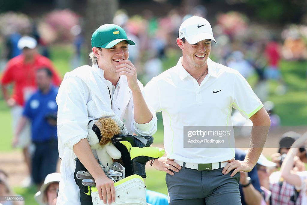 Rory McIlroy of Northern Ireland waits alongside his caddie Niall Horan of the band One Direction during the Par 3 Contest prior to the start of the 2015 Masters Tournament at Augusta National Golf Club on April 8, 2015 in Augusta, Georgia.