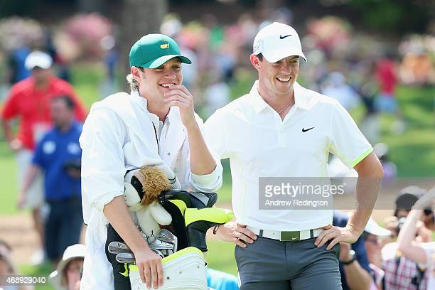Rory McIlroy of Northern Ireland waits alongside his caddie Niall Horan of the band One Direction during the Par 3 Contest prior to the start of the...