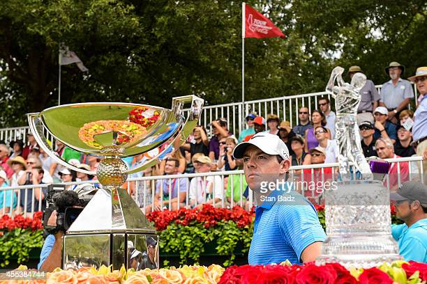 Rory McIlroy of Northern Ireland waits on the first hole tee box next to the FedExCup and TOUR Championship by CocaCola trophies during the third...