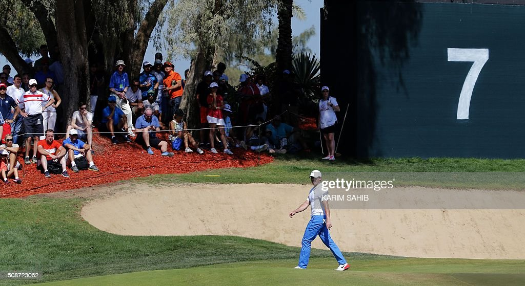 Rory McIlroy of Northern Ireland walks in the field during the third round of the 2016 Dubai Desert Classic at the Emirates Golf Club in Dubai on February 6, 2016. / AFP / KARIM SAHIB