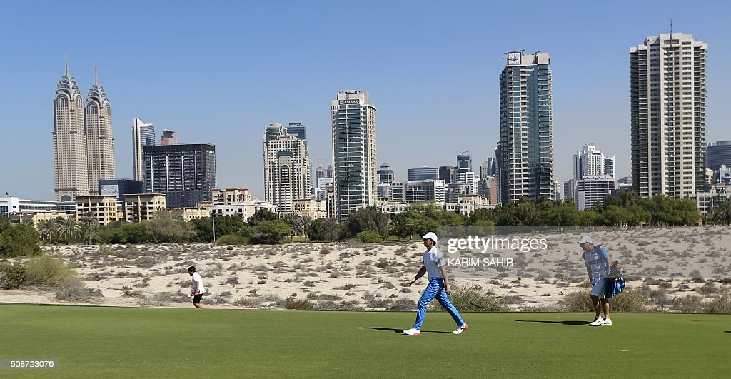 Rory McIlroy (C) of Northern Ireland walks in the field during the third round of the 2016 Dubai Desert Classic at the Emirates Golf Club in Dubai on February 6, 2016. / AFP / KARIM SAHIB