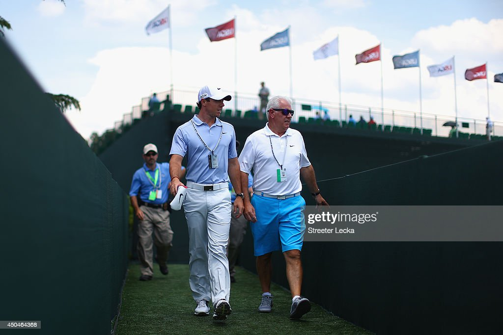 <a gi-track='captionPersonalityLinkClicked' href=/galleries/search?phrase=Rory+McIlroy&family=editorial&specificpeople=783109 ng-click='$event.stopPropagation()'>Rory McIlroy</a> of Northern Ireland walks over away from the practice range with father <a gi-track='captionPersonalityLinkClicked' href=/galleries/search?phrase=Gerry+McIlroy&family=editorial&specificpeople=5691463 ng-click='$event.stopPropagation()'>Gerry McIlroy</a> during a practice round prior to the start of the 114th U.S. Open at Pinehurst Resort & Country Club, Course No. 2 on June 11, 2014 in Pinehurst, North Carolina.