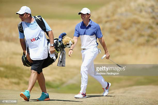 Rory McIlroy of Northern Ireland walks with caddie JP Fitzgerald across the sixth green during the final round of the 115th US Open Championship at...