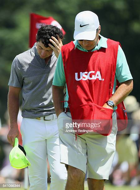 Rory McIlroy of Northern Ireland walks with his caddie JP Fitzgerald off the ninth green after finiishing the continuation of the second round of the...