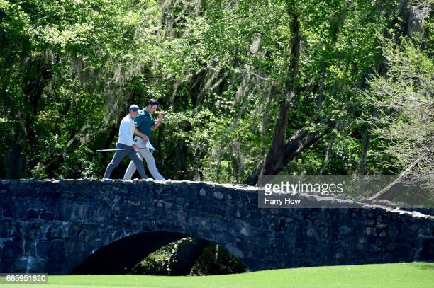 Rory McIlroy of Northern Ireland walks with Jon Rahm of Spain over the Nelson bridge during the second round of the 2017 Masters Tournament at...
