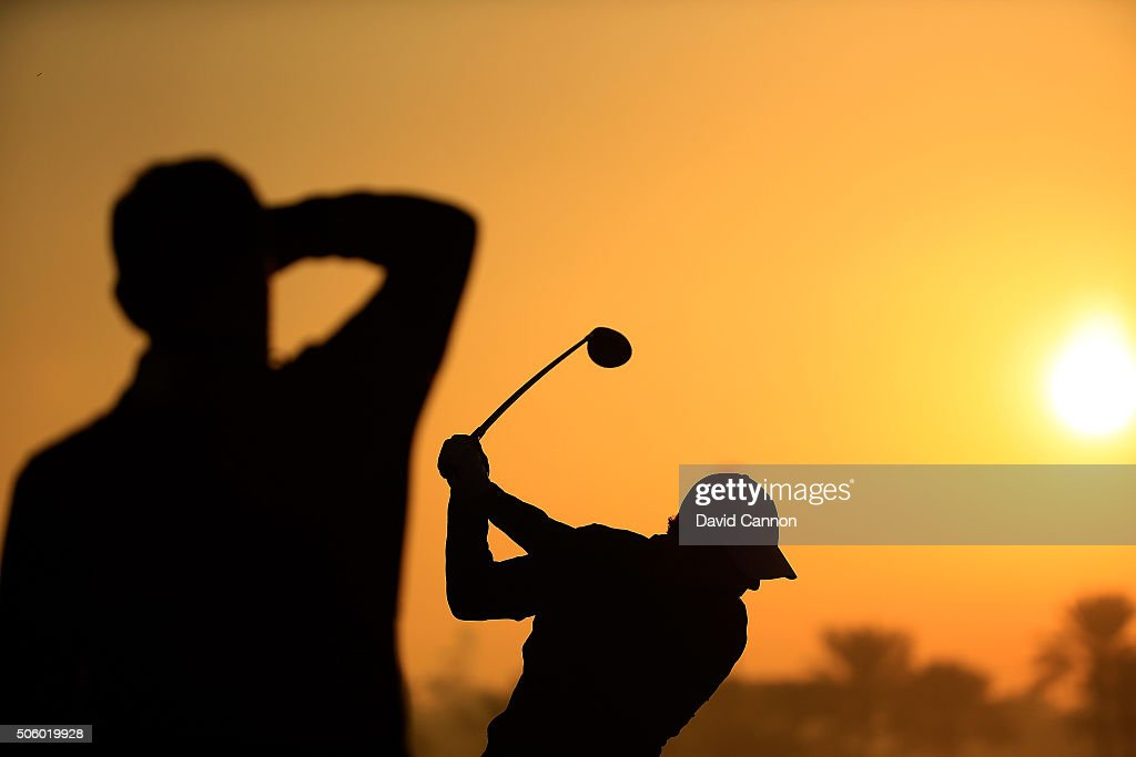 Rory McIlroy of Northern Ireland warms up on the driving range under the watchful eye of his coach Michael Bannon as the sun rises before the first round of the 2016 Abu Dhabi HSBC Golf Championship at the Abu Dhabi Golf Club on January 21, 2016 in Abu Dhabi, United Arab Emirates.