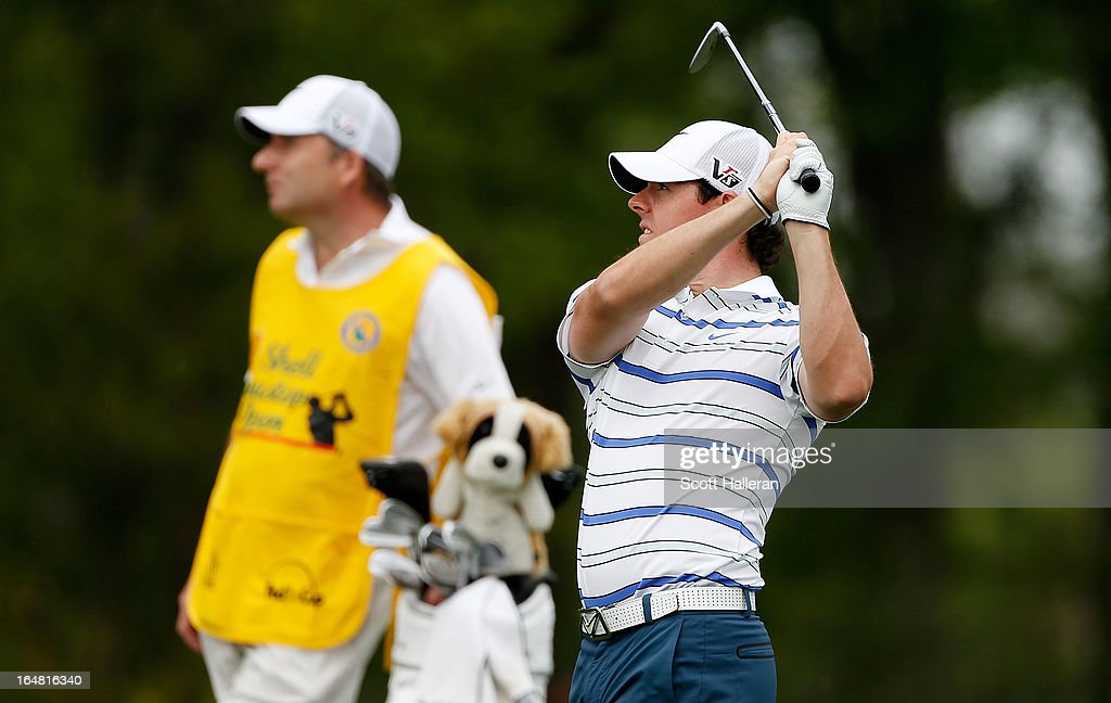 Rory McIlroy of Northern Ireland watches a shot on the second hole with his caddie J.P. Fitzgerald during the first round of the Shell Houston Open at the Redstone Golf Club on March 28, 2013 in Humble, Texas.