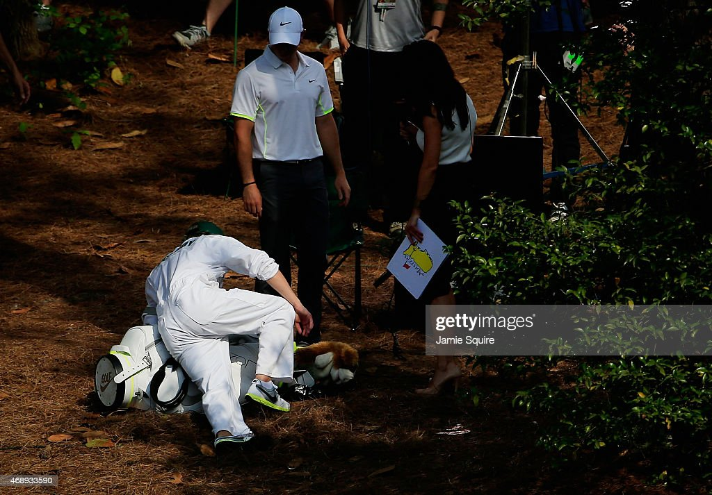 Rory McIlroy of Northern Ireland watches after his caddie Niall Horan of the band One Direction slipped on pine straw during the Par 3 Contest prior to the start of the 2015 Masters Tournament at Augusta National Golf Club on April 8, 2015 in Augusta, Georgia.