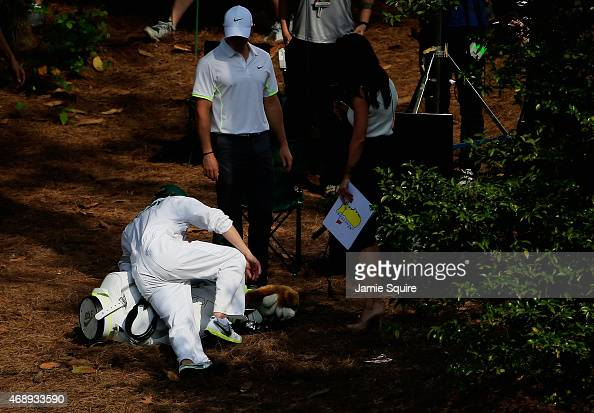 Rory McIlroy of Northern Ireland watches after his caddie Niall Horan of the band One Direction slipped on pine straw during the Par 3 Contest prior...