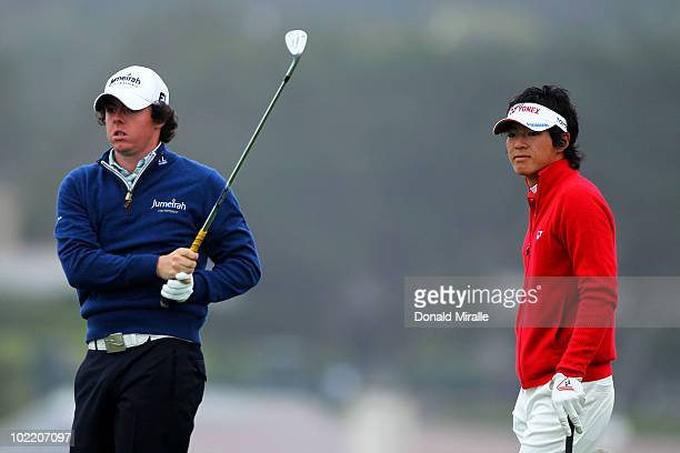 Rory McIlroy of Northern Ireland watches his tee shot on the seventh hole as Ryo Ishikawa of Japan looks on during the second round of the 110th US...