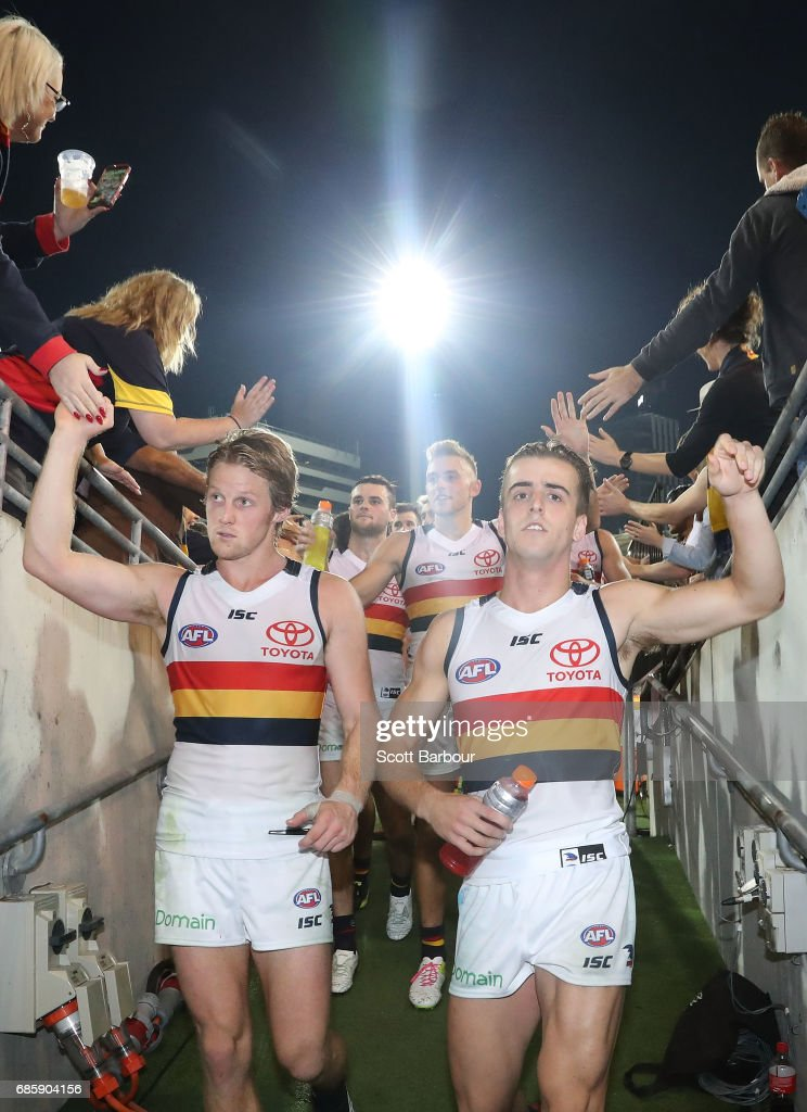 Rory Sloane and Jordan Gallucci of the Crows and their teammates leave the field after winning the round nine AFL match between the Brisbane Lions and the Adelaide Crows at The Gabba on May 20, 2017 in Brisbane, Australia.