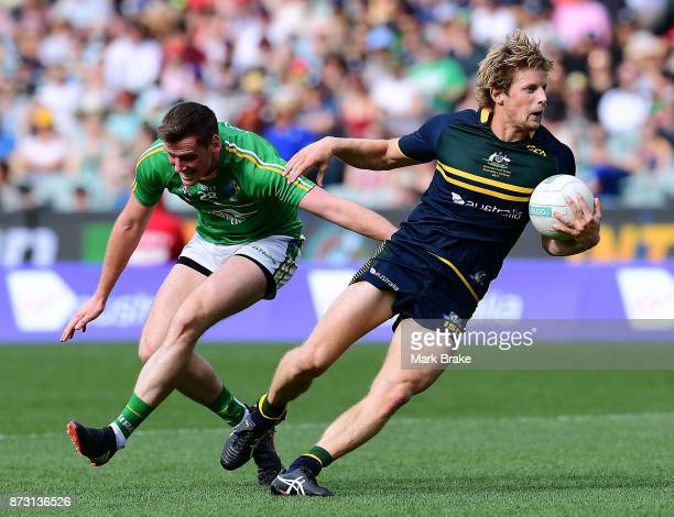 Rory Sloane of Australia gets away from Conor Sweeney of Ireland during game one of the International Rules Series between Australia and Ireland at...