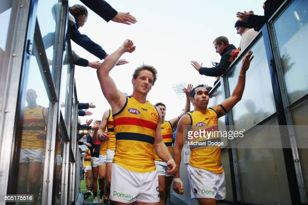 Rory Sloane of the Crows and Eddie Betts of the Crows celebrates the win with fans during the round 15 AFL match between the Carlton Blues and the...