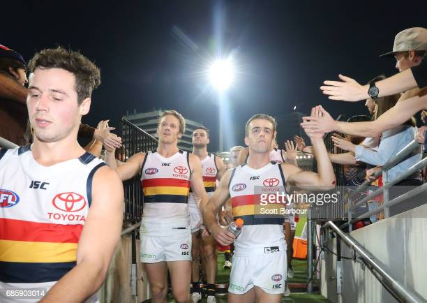 Rory Sloane of the Crows and his teammates leave the field after winning the round nine AFL match between the Brisbane Lions and the Adelaide Crows...