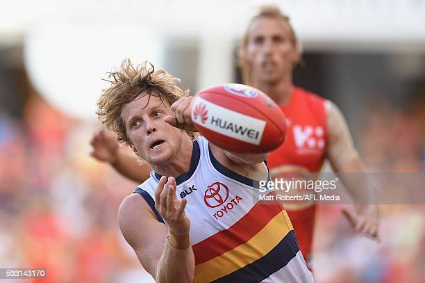 Rory Sloane of the Crows handballs during the round nine AFL match between the Gold Coast Suns and the Adelaide Crows at Metricon Stadium on May 21...
