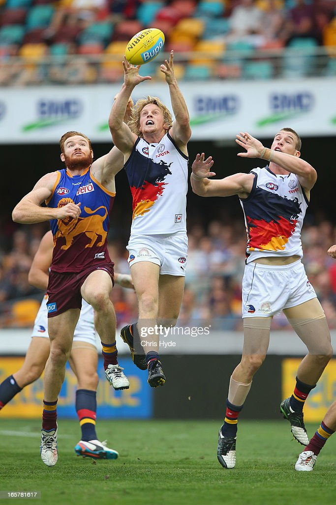 Rory Sloane of the Crows marks the ball over Daniel Merrett of the Lions during the round two AFL match between the Brisbane Lions and the Adelaide Crows at The Gabba on April 6, 2013 in Brisbane, Australia.