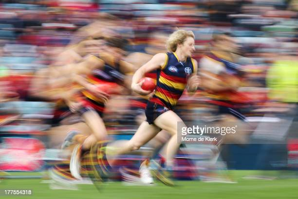 Rory Sloane of the Crows runs with the ball before the round 22 AFL match between the Adelaide Crows and the Melbourne Demons at AAMI Stadium on...