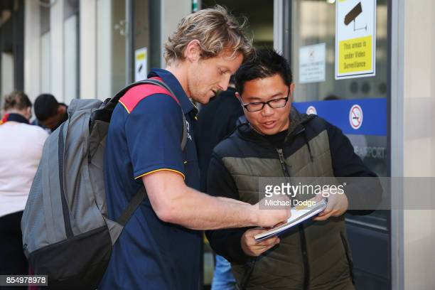 Rory Sloane of the Crows signs autographs for fans on arrival at Melbourne Airport on September 28 2017 in Melbourne Australia Adelaide will play...