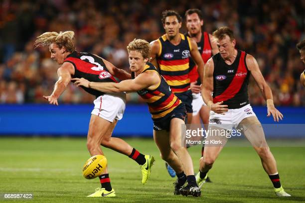 Rory Sloane of the Crows tackles Darcy Parish of the Bombers during the round four AFL match between the Adelaide Crows and the Essendon Bombers at...