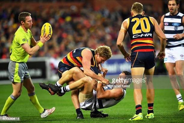 Rory Sloane of the Crows wrestles with Harry Taylor of the Cats after receiving a high tackle during the round 18 AFL match between the Adelaide...