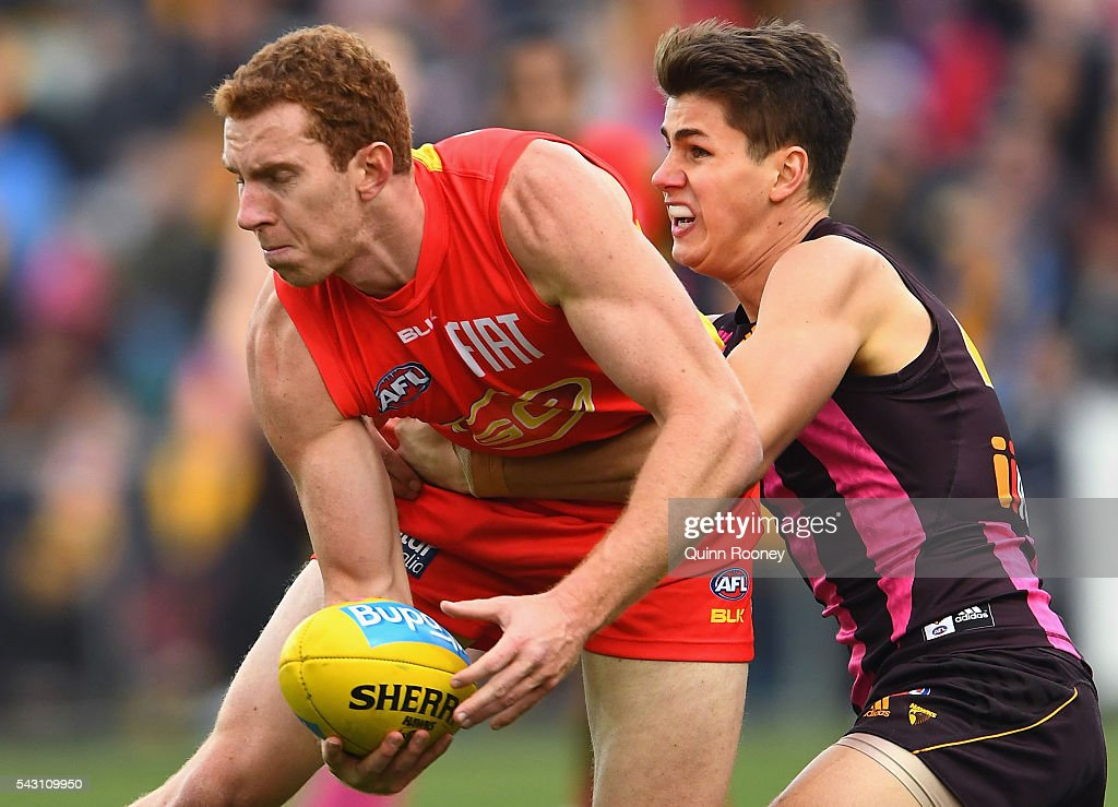 Rory Thompson of the Suns is tackled by Daniel Howe of the Hawks during the round 14 AFL match between the Hawthorn Hawks and the Gold Coast Suns at Aurora Stadium on June 26, 2016 in Launceston, Australia.