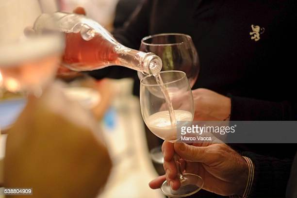 Rosé sparkling wine being poured in a glass during a degustation party