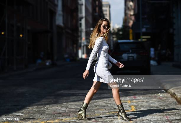 Rosa Crespo is seen in Soho wearing a Naked Wardrobe white dress Chiara Ferragni Collection gold boots and Laurencecchi backpack on August 22 2017 in...