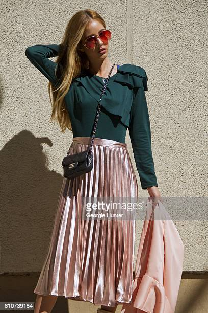Rosa Crespo wearing silk bubblegum pink pleated midi length high waisted El Corte Ingles lame skirt green long sleeve Sandro Paris top with ruffle...