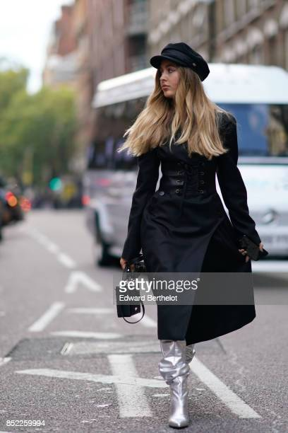 Rosa Crespo wears a beret hat a black dress a corset silver boots during London Fashion Week September 2017 on September 16 2017 in London England
