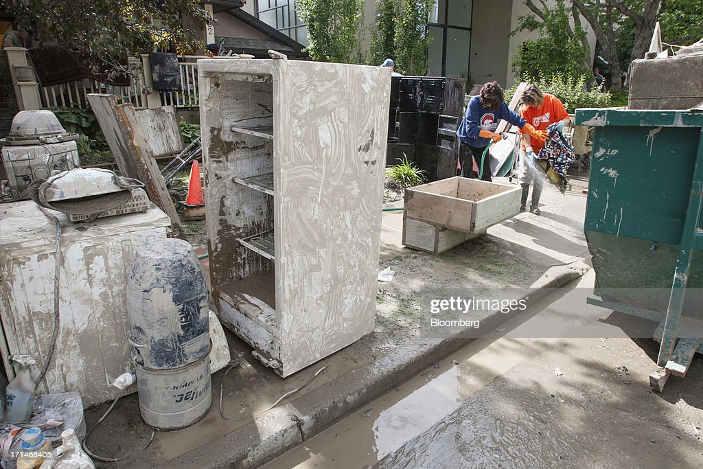 Rosa McDonald, left, and Angela Dearlove spray down a friend's belongings on Rideau Road SW after flooding in Calgary, Alberta, Canada, on Monday, June 24, 2013. Water levels in Calgary subsided and crews are working to restore power as officials confirmed a fourth fatality in the worst flood in Alberta's history. Photographer: Keith Morison/Bloomberg via Getty Images