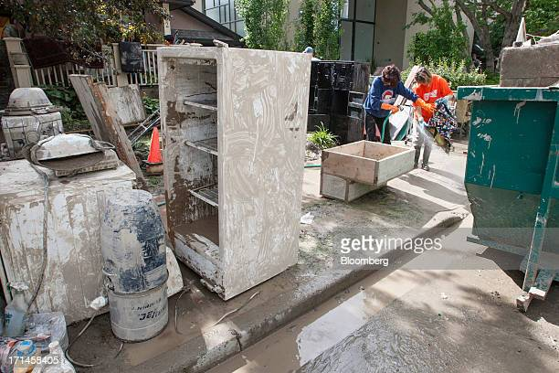 Rosa McDonald left and Angela Dearlove spray down a friend's belongings on Rideau Road SW after flooding in Calgary Alberta Canada on Monday June 24...