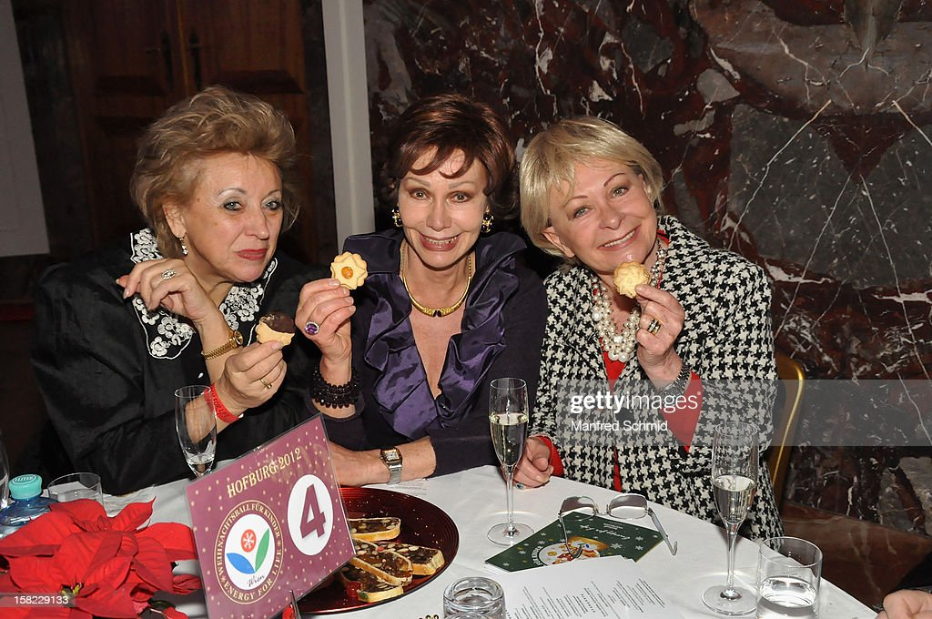 Rosalinde Haller, Edith Leyrer and Brigitte Neumeister taste a bsicuit at the Christmas ball for children Energy For Life - Heat For Children's Hearts at Hofburg Vienna on December 11, 2012 in Vienna, Austria.