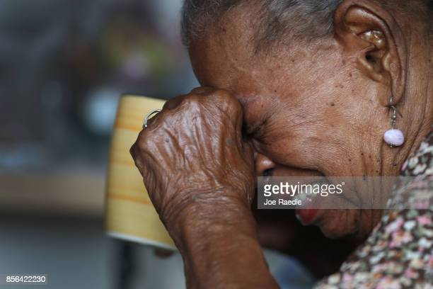 Rosario LugoLopez grimaces as she takes her medication while receiving medical care from the First Medical Relief team at the Pedro America Pagan de...