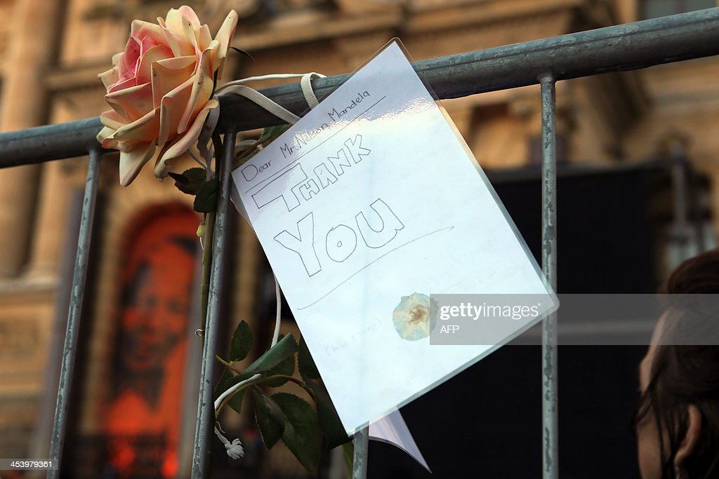 A rose and a thank you card adressed to late South African former president Nelson Mandela hang from a railing outside Cape Town's City Hall on December 6, 2013 during an inter-faith service in honour of Mandela held at the nearby Grand Parade, where Mandela made his first speech as a free man in 1990. Mandela, the revered icon of the anti-apartheid struggle in South Africa and one of the towering political figures of the 20th century, died in Johannesburg on December 5 at age 95. Mandela, who was elected South Africa's first black president after spending nearly three decades in prison, had been receiving treatment for a lung infection at his Johannesburg home since September, after three months in hospital in a critical state. AFP PHOTO/JENNIFER BRUCE