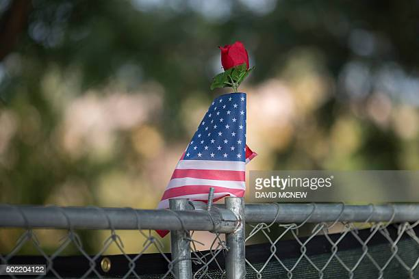 TOPSHOT A rose and flag stand atop a fence surrounding the perimeter of the Inland Regional Center site of the massacre by suspects Syed Farook and...
