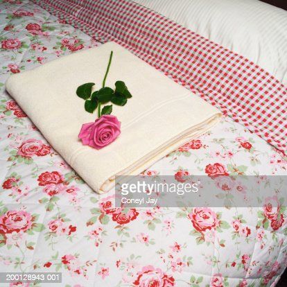 Rose and towel on floral patterned bedspread