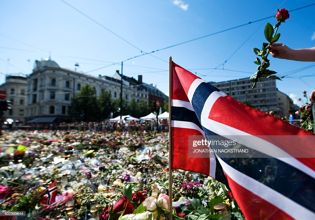 A rose being placed next to a Norwegian flag at a makeshift memorial outside the Cathedral in Oslo in honor of the 76 victims of the July 22 twin...
