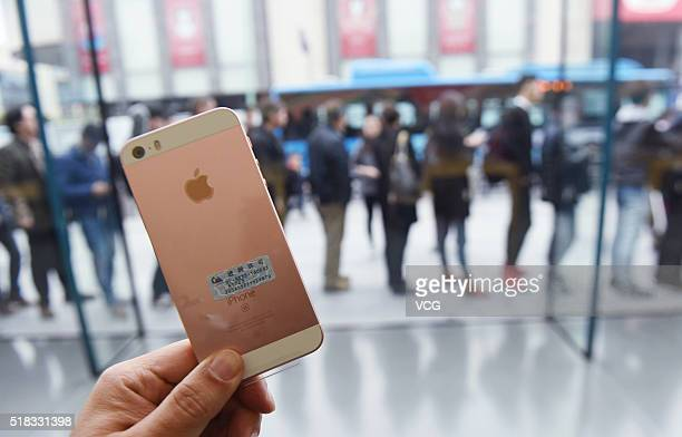 A rose gold iPhone SE is purchased by a customer at an Apple Store on March 31 2016 in Hangzhou Zhejiang Province of China Apple launched a new 4inch...