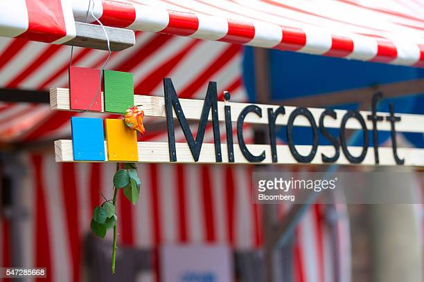 A rose hangs from the Microsoft Corp logo on the company's startup accelerator stand at the Tech Open Air conference in Berlin Germany on Thursday...