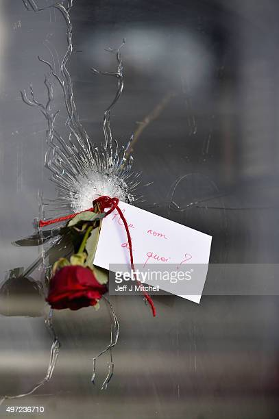 A rose is placed beside a bullet hole at La Belle Equipe restaraunt on Rue de Charonne following Fridays terrorist attack on November 15 2015 in...