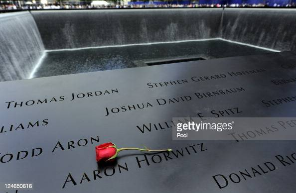 A rose is placed next to an inscribed name along the wall of the North Pool of the 9/11 Memorial during the tenth anniversary ceremonies of the...