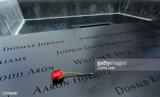 A rose is placed on the names inscribed around the North Pool of the 9/11 Memorial during tenth anniversary ceremonies at the site of the World Trade...