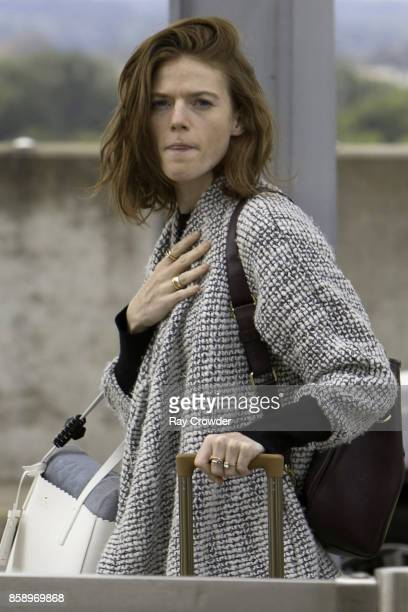 Rose Leslie shows off her engagement ring as she arrives at Heathrow airport to catch a flight on October 8 2017 in London England